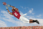 Black football player catching football in mid-air