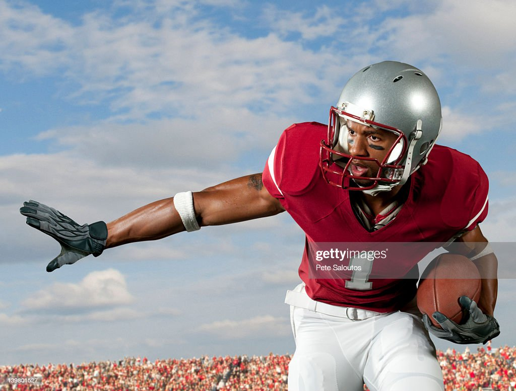 Black football player holding football : Stock Photo