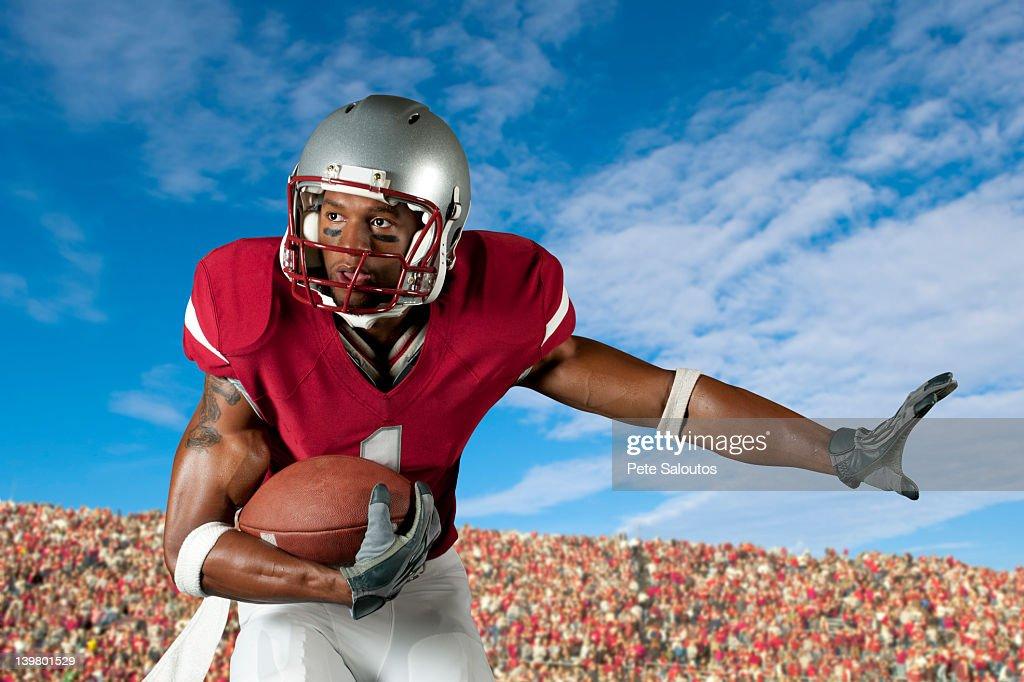 Black football player holding football : Stock Photo