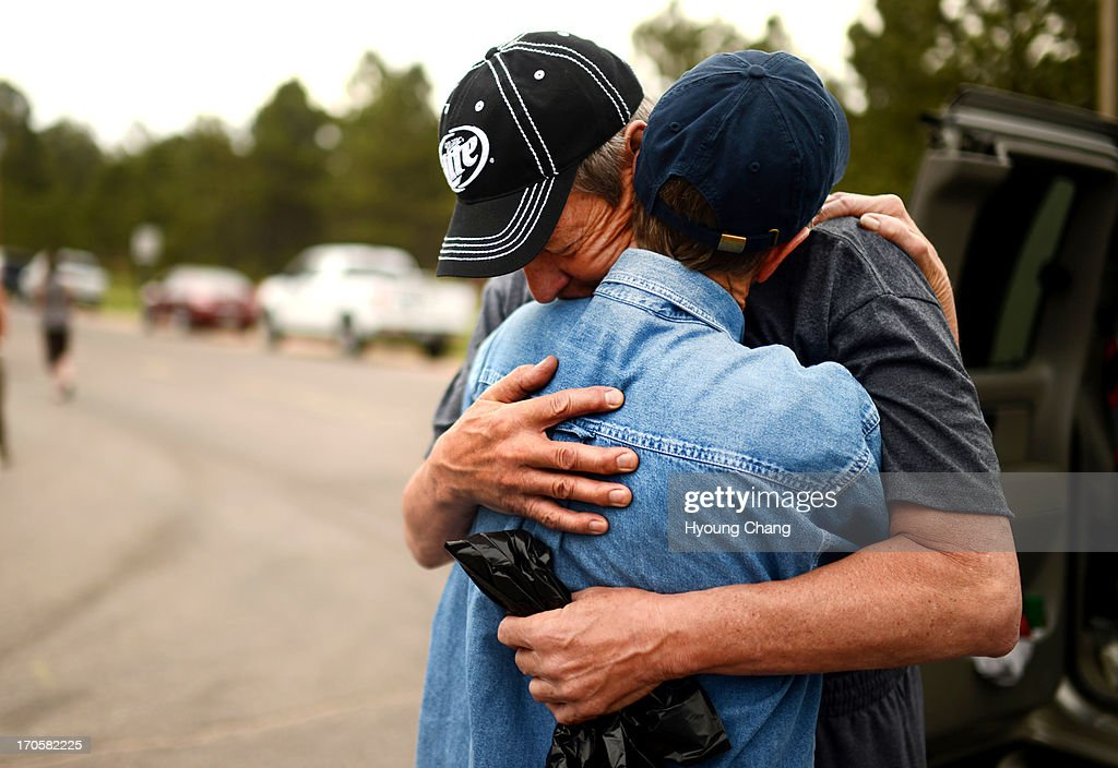 Black Forest Fire evacuees Cindy Miller hugs her husband Ray before his going to their property with El Paso County Sheriff's escort at the corner of...