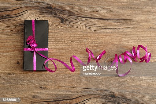 black gift box decorated with a pink ribbon : Stock Photo