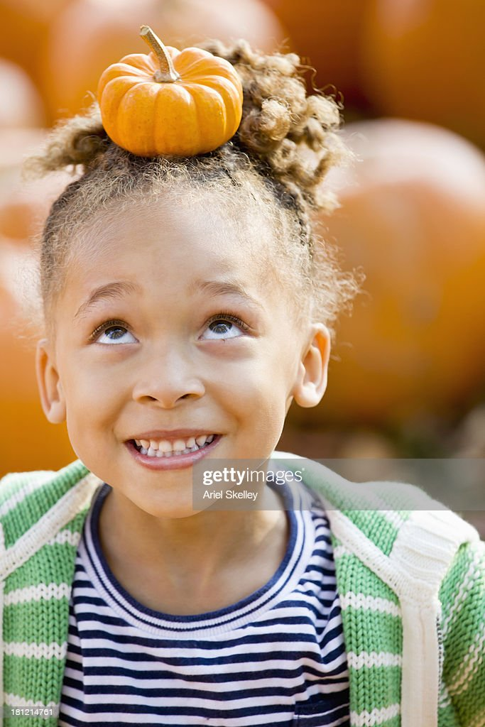 Black girl balancing pumpkin on head : Stock Photo