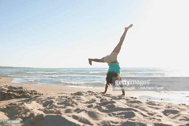 Black girl doing cartwheels on beach