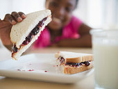 Black girl eating peanut butter and jelly sandwich