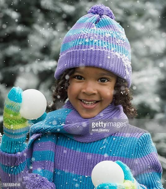 Black girl holding snowballs