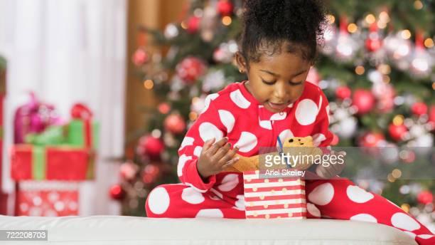 Black girl holding teddy bear toy on Christmas