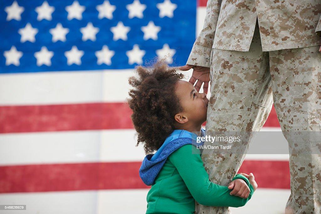Black girl hugging leg of returning soldier