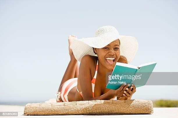 black girl in bikini and sun hat, at the
