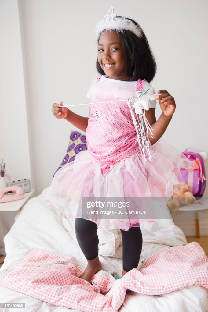Black girl in fairy costume standing on bed : Stock Photo