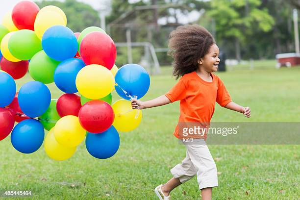 Black girl in park running with large bunch of balloons