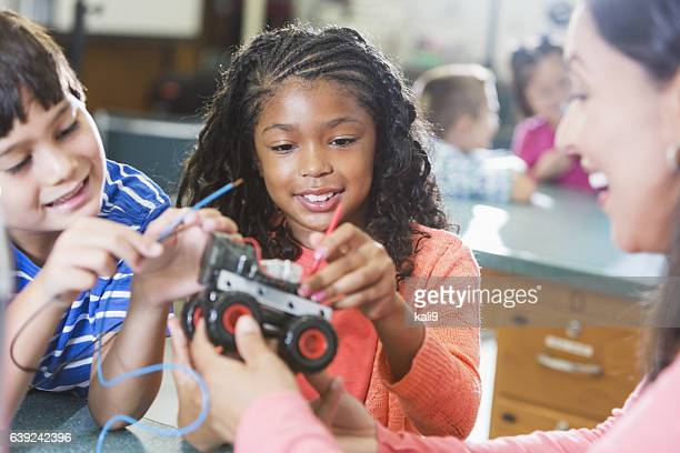 Black girl in science class learning robotics