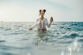 Charming young black curly lady in traditional African chemise standing up to the waist in teal seawater and holding beads in her left hand, strong reflection in the bottom, ripples on water surface