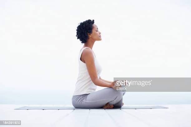 Black girl meditating - bright background with copy space
