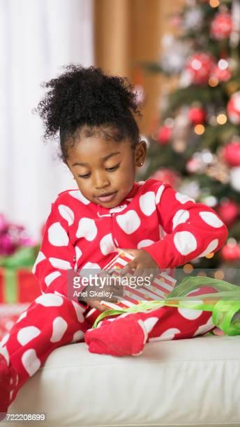 Black girl opening gift box on Christmas