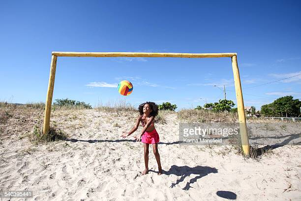 Black girl playing with a football on the sand