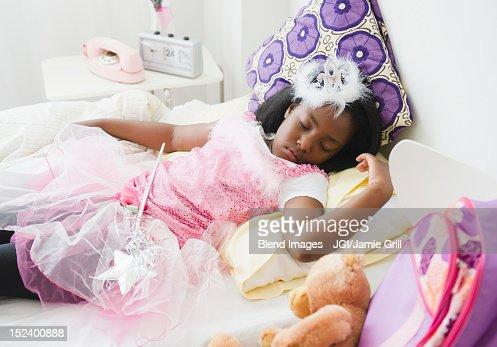 Black girl sleeping in fairy costume : Stock Photo