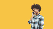 Cheerful cute young African American female student smiling while having phone conversation, standing in front of solid isolated yellow background with copy space place for advertising, text or logo
