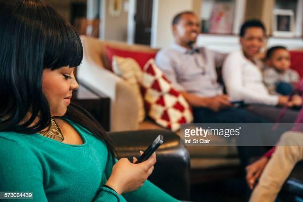 Black girl using cell phone in living room