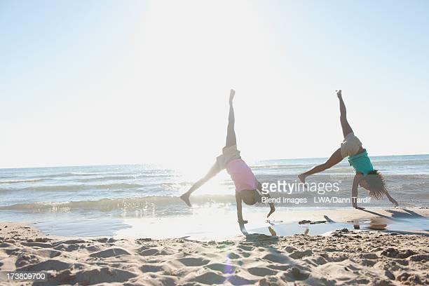Black girls doing cartwheels on beach