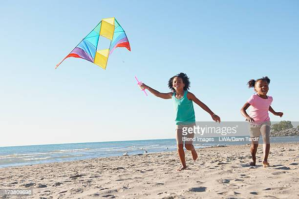 Black girls flying kites on beach