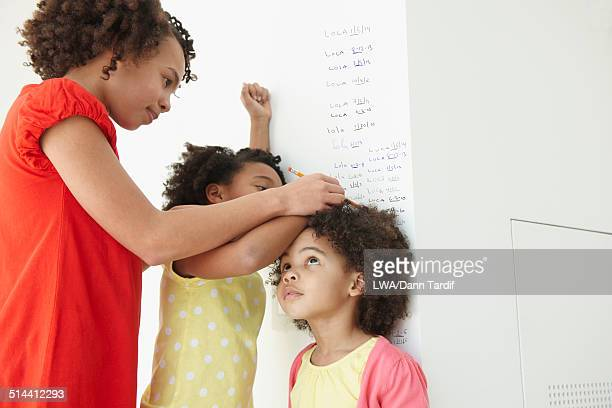 Black girls measuring their height on wall