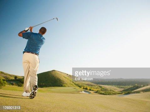 Black golfer swinging golf club