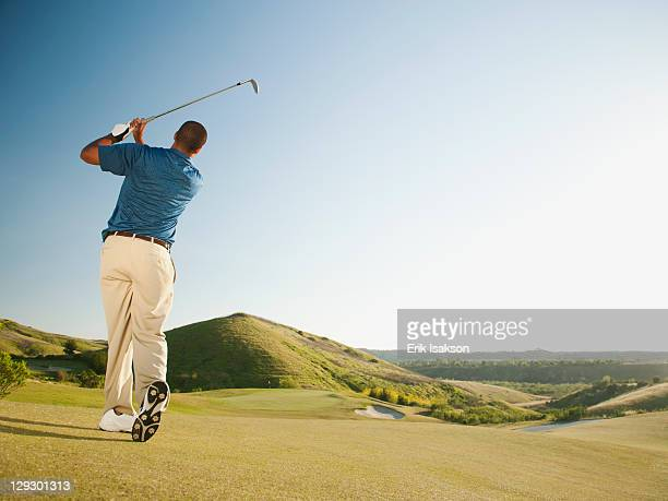 Black golfer swinging golf club