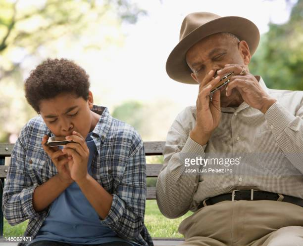 Black grandson and grandfather playing harmonica together in park