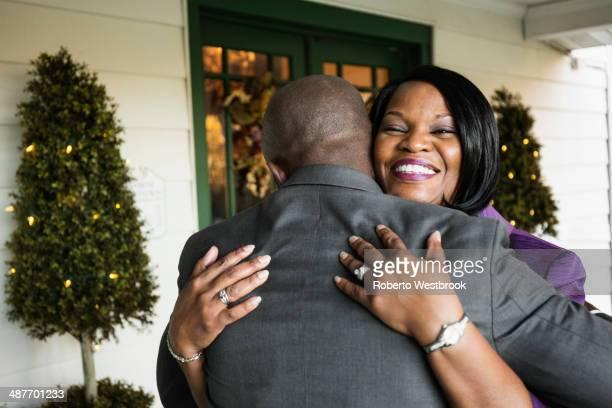 Black groom hugging mother at wedding
