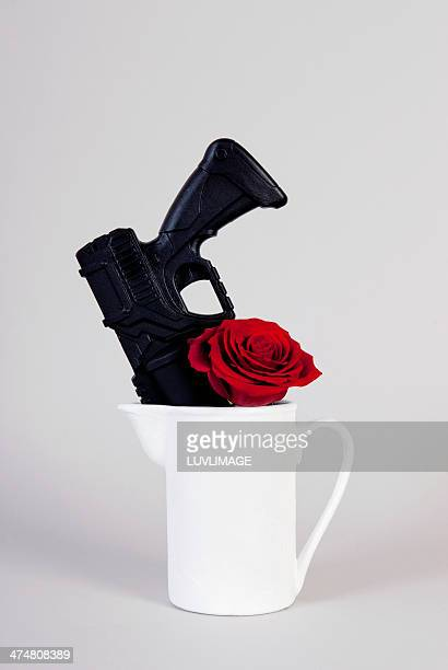 Black gun in water pot with red rose