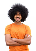 Portrait of a young black guy smiling with arms crossed against white background