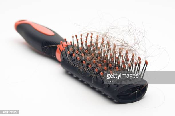 Black hairbrush showing that its owner has hair loss