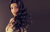 Young black haired woman  with voluminous, shiny and wavy hair . Beautiful model with long, dense and curly hairstyle. Frizzy hair.