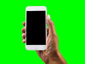 Hand holding mobile smart phone with blank screen, isolated cutout on green background with chroma key