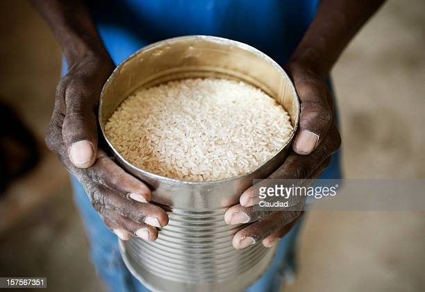 Black hands holding can of rice