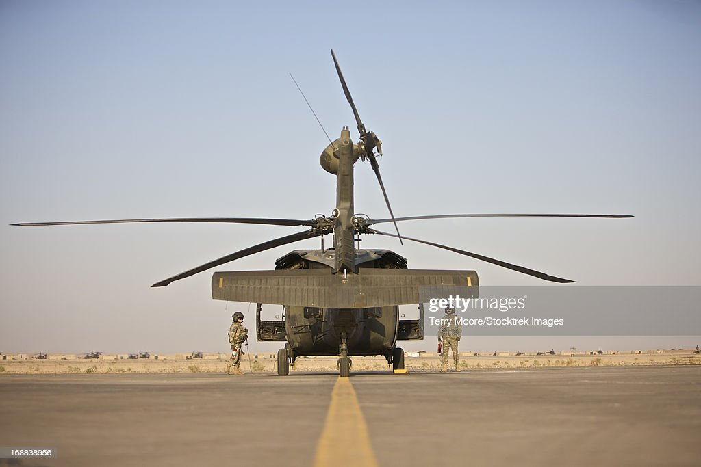 UH-60 Black Hawk flight crew members standby with fire extinguishers on startup, Tikrit, Iraq.