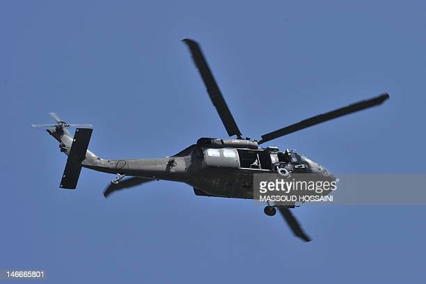 Black Hawk helicopter flies near the Spozhmai Hotel in Qargha lake in the outskirts of Kabul on June 22 2012 Taliban militants armed with guns and...