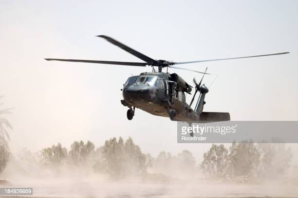 Black Hawk helicopter hovering above a dusty ground