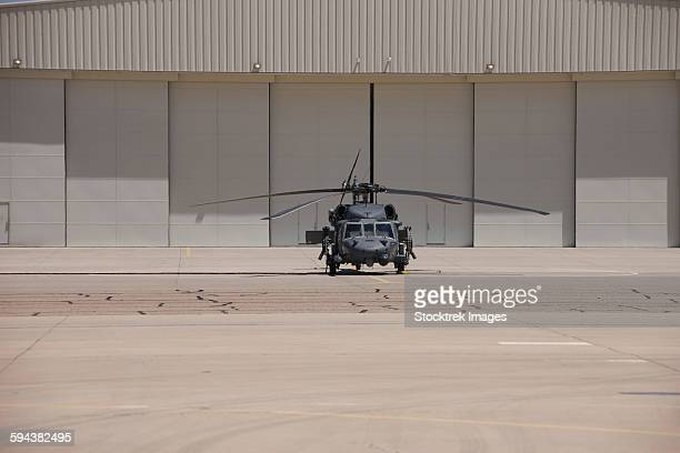 A UH-60 Black Hawk helicopter parked in front of a hanger.