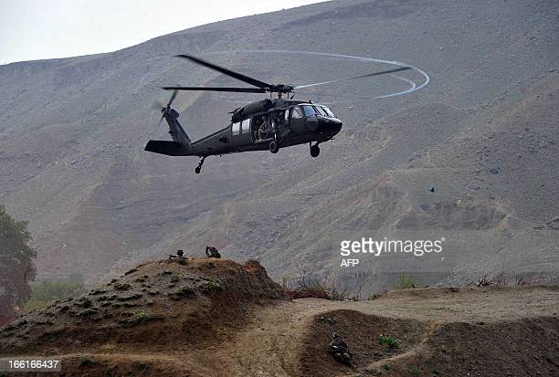 Black Hawk helicopter prepares to land near the scene of a helicopter crash during a recovery operation in the Pachir Wa Agam district of Nangarhar...