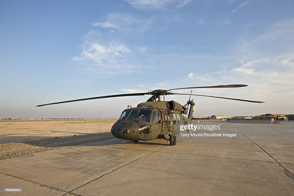 A UH-60 Black Hawk parked on the maintenance pad at a military base in Tikrit, Iraq.