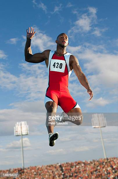 Black high jumper in mid-air at track & field event