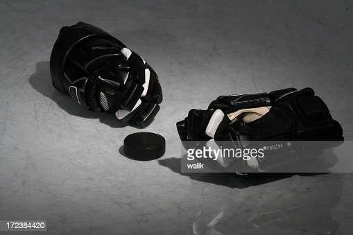 Black hockey equipment laying on an ice rink
