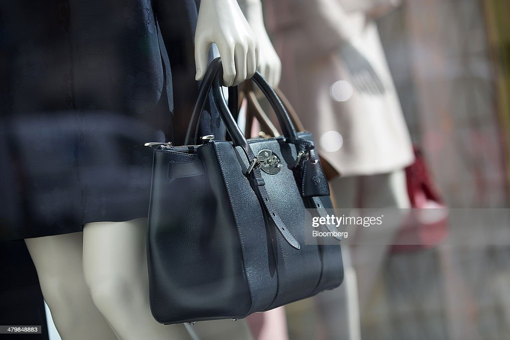 A black ladies bag hangs from a mannequin's hand in the window of a Mulberry Group Plc luxury store on New Bond Street in London, U.K., on Thursday, March 20, 2014. Mulberry Group said Bruno Guillon will step down as chief executive officer after two years during which the British luxury handbag maker lost two-thirds of its market value. Photographer: Simon Dawson/Bloomberg via Getty Images