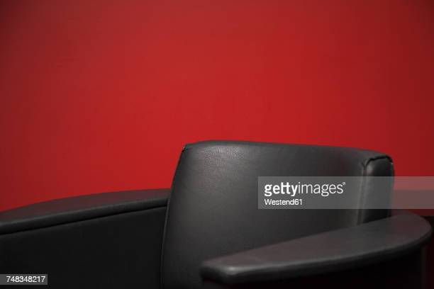 Black leather chair in front of red wall, partial view
