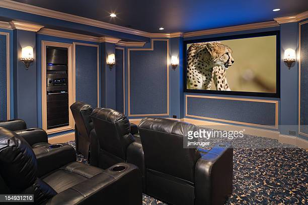 Black leather chairs adorn a beautiful home theatre.