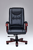 Executive black leather office chair over white ground with wooden handles and legs.