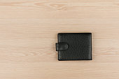 Black leather purse lying on a wooden table. View from above