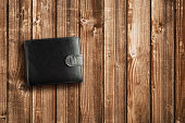 Black leather wallet on wooden table