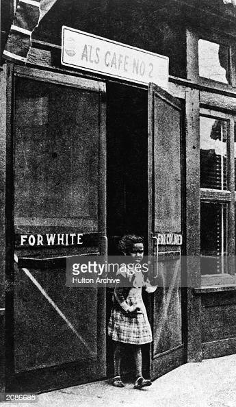 A black little girl leaves a cafe through a door marked 'For Colored' circa 1950